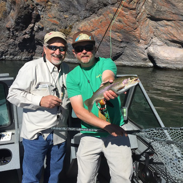 Jeff Perin in his boat with a client holding a big rainbow on one of central oregons cascade lakes